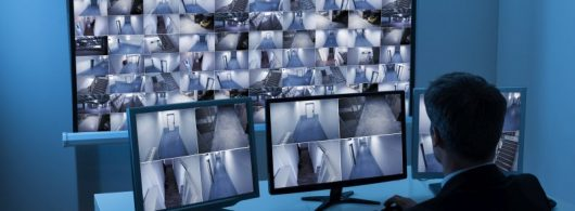 Rear View Of A Man In Control Room Monitoring Multiple Cctv Footage