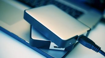 Portable Hard Drives Backup System. Two Portable Hard Drives on the Laptop Closeup Photo.